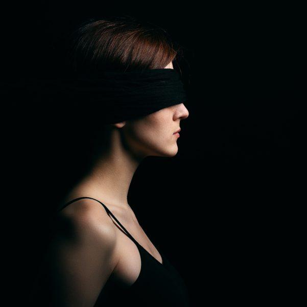 Bird-Box-Challenge: Frau mit verbundenen Augen vor schwarzem Hintergrund