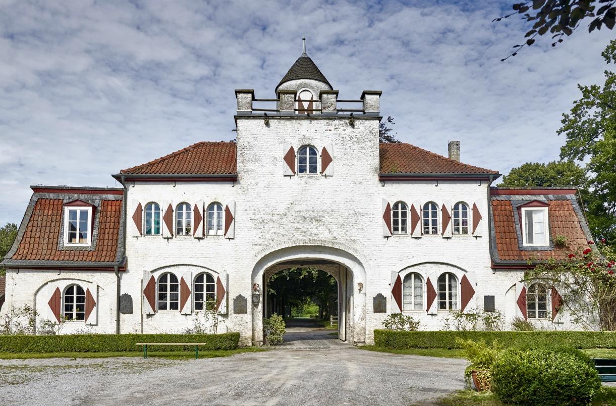 Bild zeigt: Vorderansicht des Gut Heimendahl. Ein weißes dreigeschossiges Gebäude mit Hoftor.