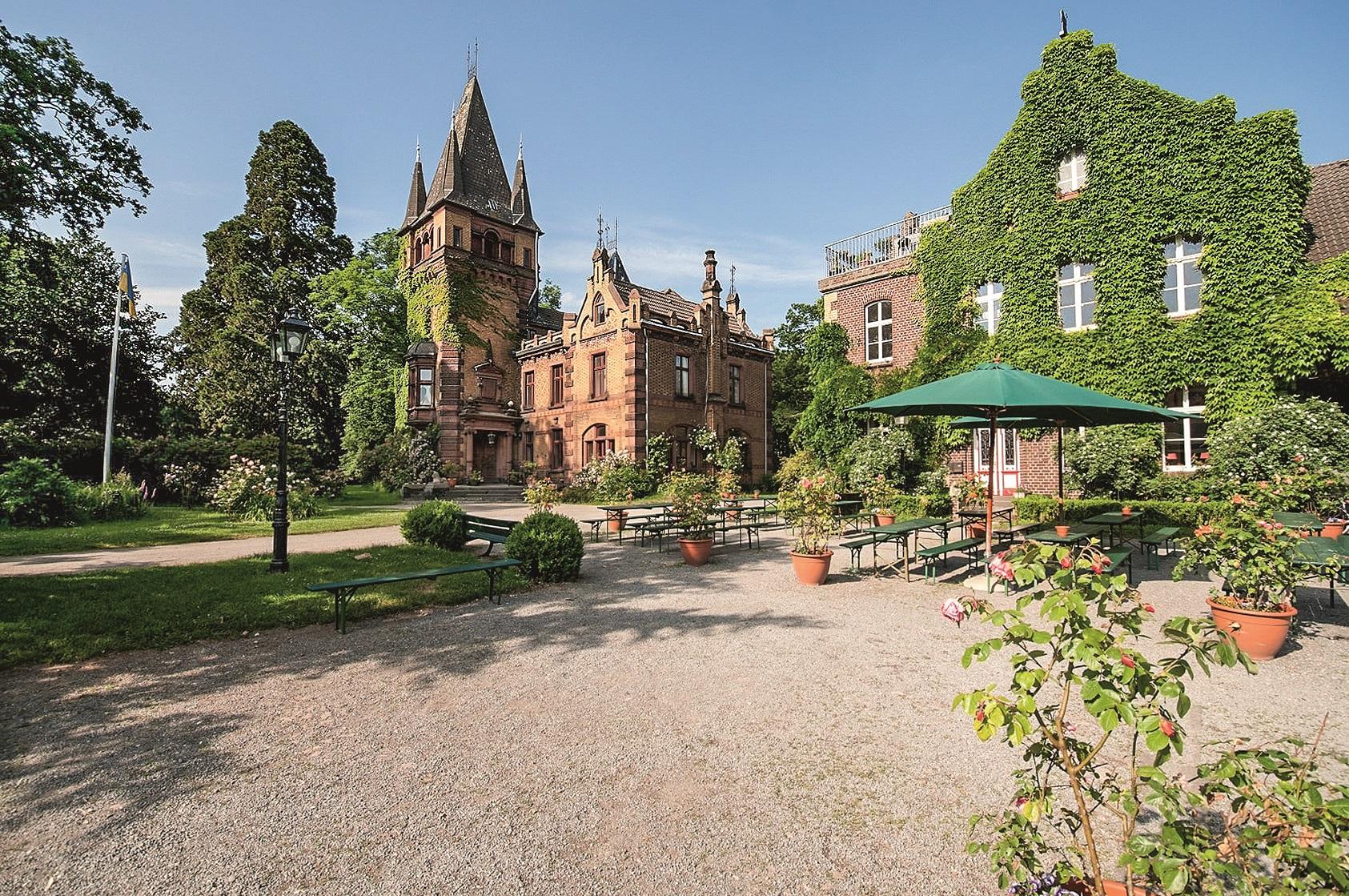 Bild zeigt den Innenhof des Gut Heimendahl. Ein begrünter Platz mit Tischen und Bänken sowie einem Sonnenschirm.