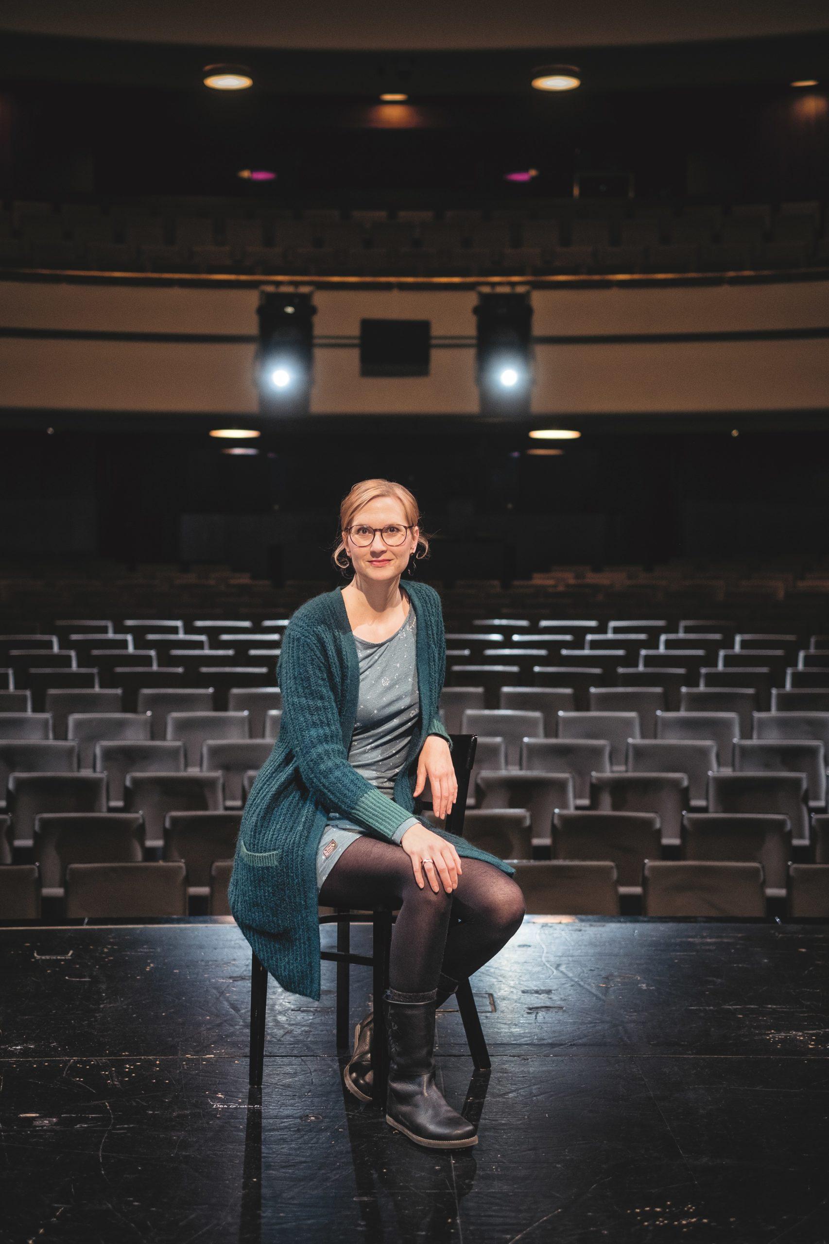 Bild zeigt: Rike Oberländer. Sie sitzt im leeren Theater auf der Bühne auf einem Stuhl