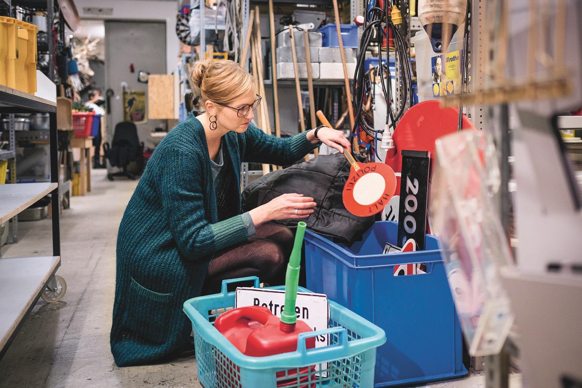 Bild zeigt: Rieke Oberländer im Theater-Fundus. In einem Korb sammelt sie Requisiten zusammen.